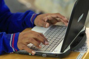 niño utilizando un aparato electronico reciclado
